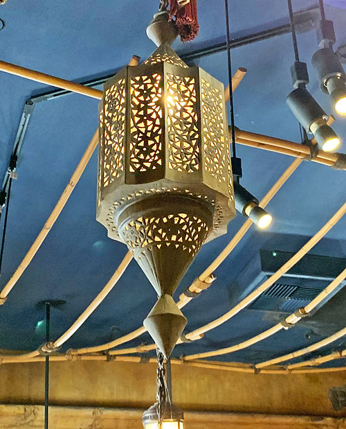 Metal light fixture hanging from ceiling of Adventureland Bazaar in Disneyland