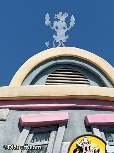 Clarabelle Cow holding 2 ice cream cones on roof of Clarabelle's Snack Stand in Mickey's Toontown Disneyland