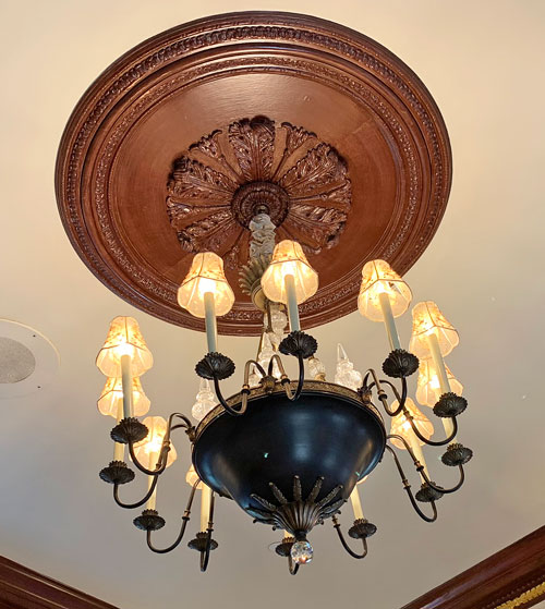Chandelier with carved wood medallion at Disneyland Club 33