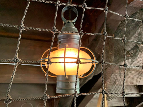 Hanging lantern style light fixture behind knotted rope on the Jungle Cruise Attraction in Adventureland Disneyland