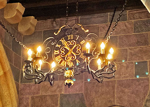 Hanging light fixture clock with Roman numerals and faux candles in Sleeping Beauty Castle Disneyland
