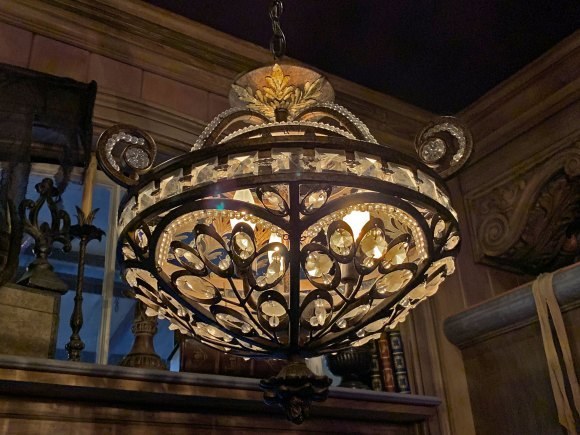 Ornate crystal glass and metal chandelier hanging in Port Royal Curios and Curiosities Shop in New Orleans Square Disneyland