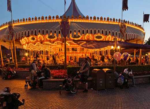 King Arthur Carrousel lit up at dusk with a warm glow in Fantasyland at Disneyland
