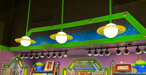 3 light fixtures shaped liked planet Saturn with rings hanging from ceiling in Little Green Men Command Store in Tomorrowland Disneyland