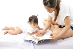 Mother Is Reading A Book For Her Baby