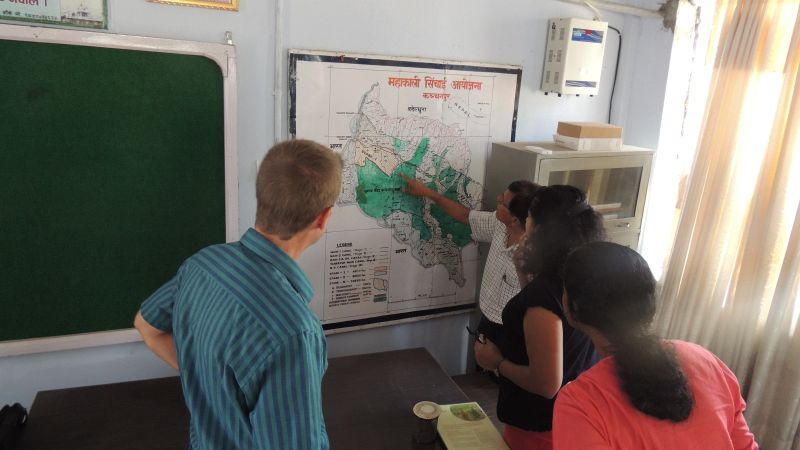 IWMI staff and partners glance at a map of Far West Nepal.