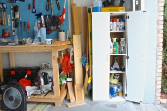 """Workshop"" side of the garage. Shelf cabinet packed with junk, spare wood, brooms... a bit on the messy side."