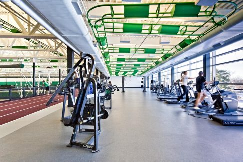 The track itself opens to a cardio-fitness area featuring a curtain wall that draws natural light deep into the space and connects the interior fitness areas to the synthetic turf football field and outdoor running track