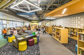 """The library acts as a """"learning corridor"""". Space is not differentiated between circulation and the media center, instead they blend together and become a functional learning space."""