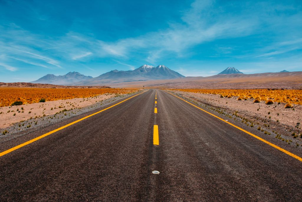 road with yellow line down the middle fading into mountains in the horizon