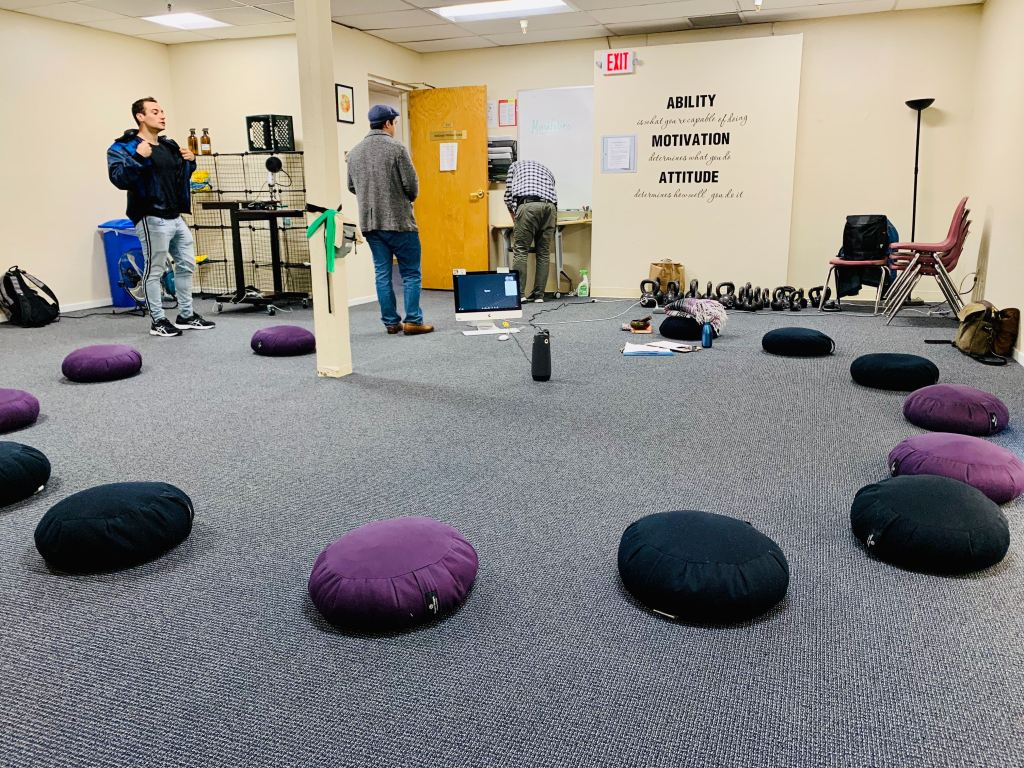 A class at MIIS recently used an Owl (located in the middle of the circle) to welcome online participants into their physical circle