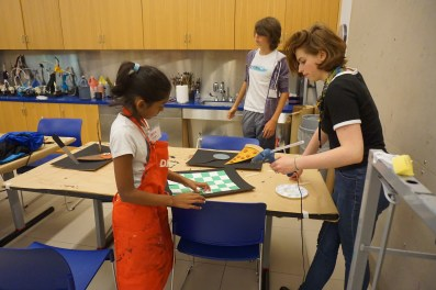 Annabella helps a camper make her creative vision a reality.