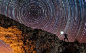 Circumpolar trazas de estrellas startrails sobre un arco de piedra natural. Fotografía nocturna