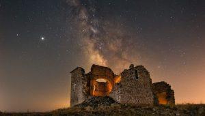 Fotografía Nocturna de larga exposición donde se muestra las ruinas de la ermita de Santa Ana y la vía láctea