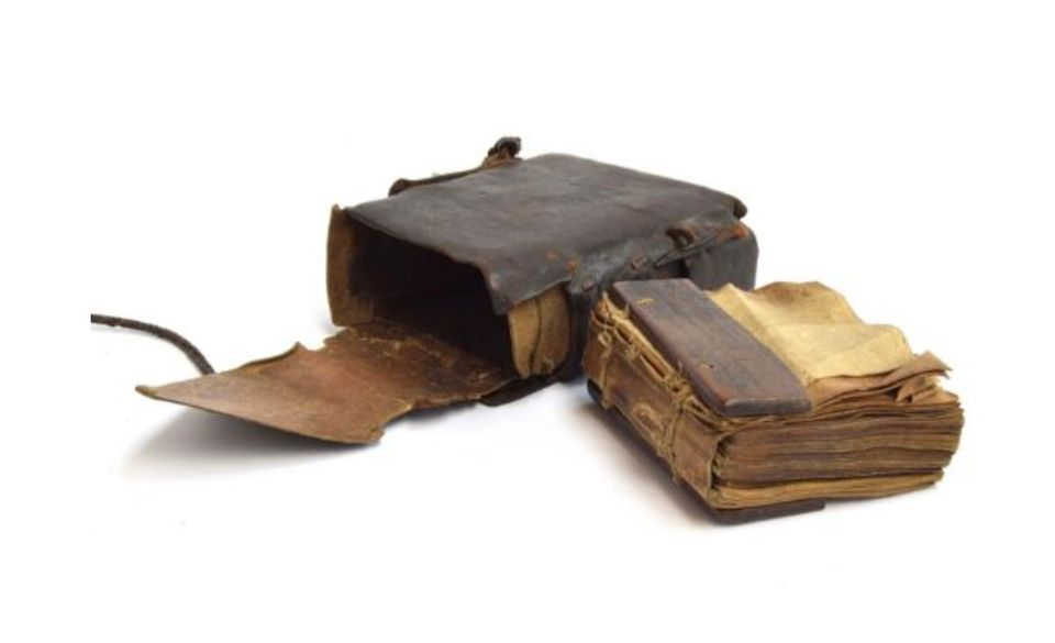 The Coptic bible, dating from the early- to mid-18th century, is bound in a leather purse together with a metal cross