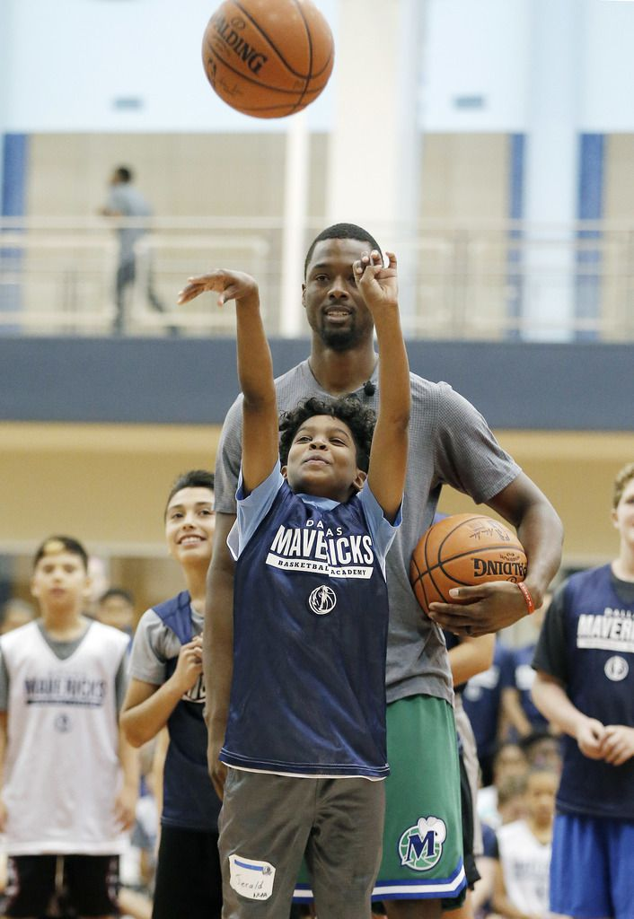 Jerald Harper competes against Dallas Mavericks forward Harrison Barnes in a game of knockout during the Mavs Basketball Academy Hoop Camp.