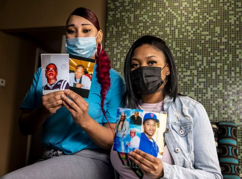 Cousins Nicole Hill (left) and Netia Smith hold photos of deceased brothers Isaac (second from left) and Ishmael Mozeke (left) at Smith's apartment in Dallas. The cousins, particularly Hill, were longtime family friends of the Mozeke brothers, both of whom died by gun violence two decades apart.