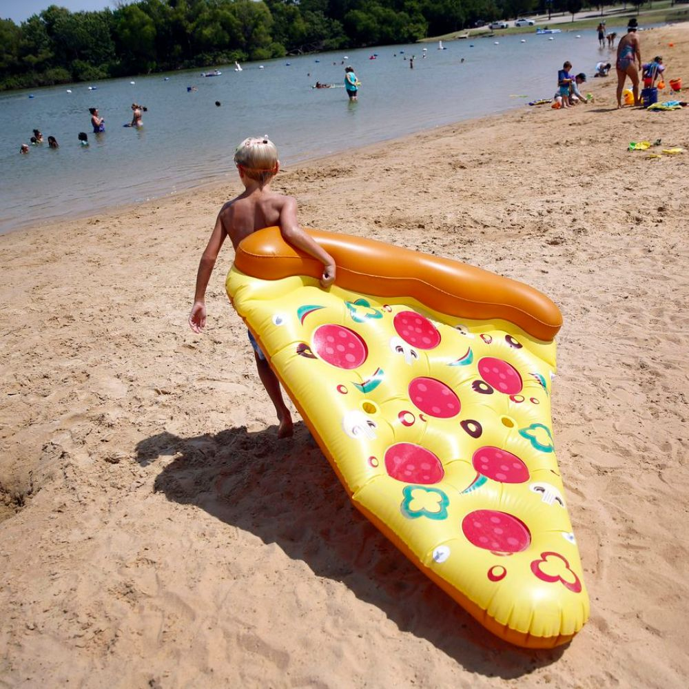 Camden Clark,10, of Frisco drags his inflatable slice of pizza across Little Elm Park beach to Lake Lewisville in Little Elm, Texas, Thursday, July 16, 2020.