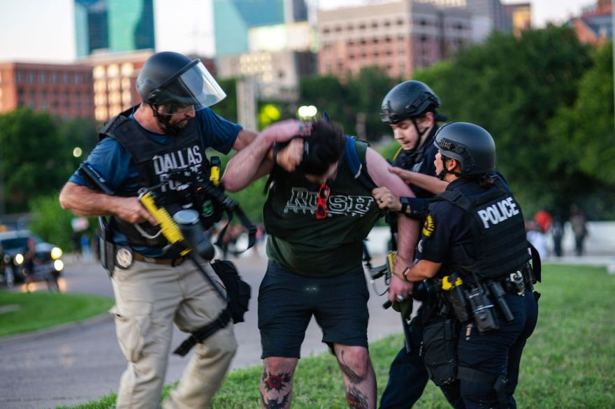 Dallas police Sgt. Roger Rudloff (left) grabs Parker Nevills by his ponytail as other officers take him to the ground during George Floyd protests last year.