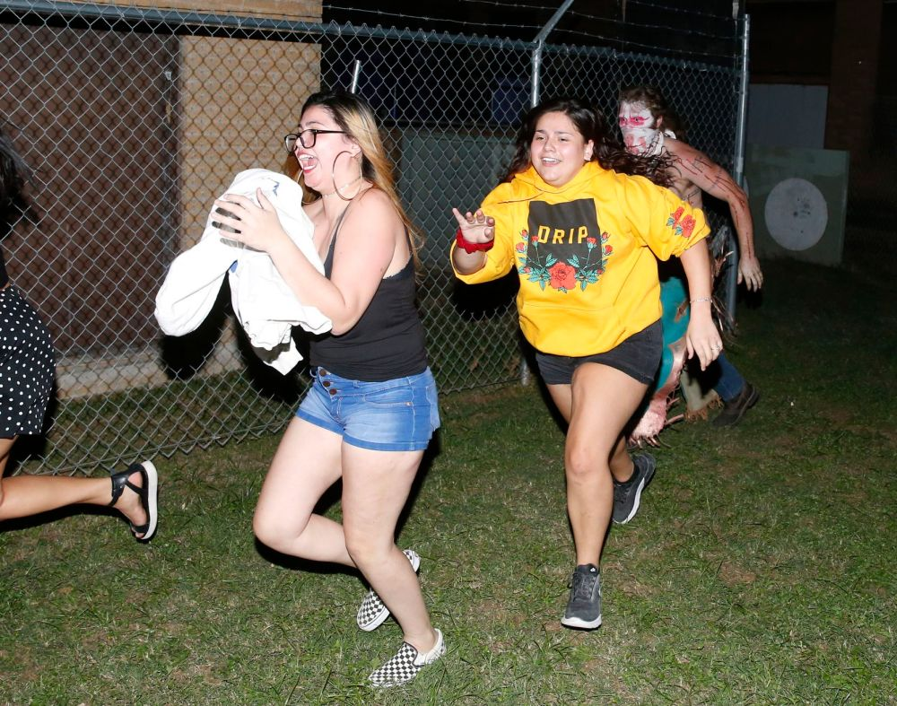 """Jessie Reyes (left), Hannah Reyes (center) run from Marshal McKelvy (right) """"Tex,"""" as they make their way out of Texas Scaregrounds' Nazareth Hospital in Mineral Wells in 2020."""