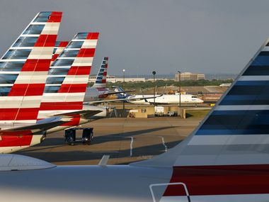 American Airlines jets are parked at Terminal C as a Skywest jet taxis to the gate at Dallas-Fort Worth International Airport on April 19, 2020.