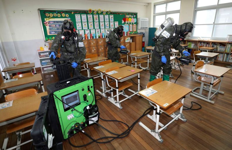 South Korean army soldiers sprayed disinfectant to help reduce the spread of the new coronavirus in a class at Cheondong elementary school in Daejeon in early July.