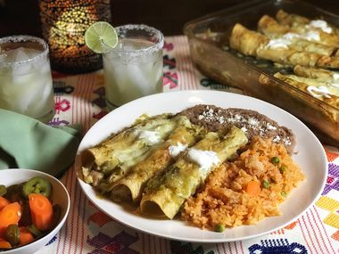 A plate of enchiladas verdes, Mexican rice and refried beans