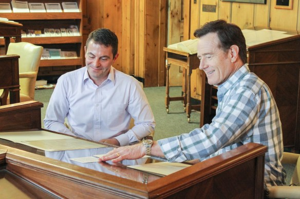 Bryan Cranston and Christopher look over a document.