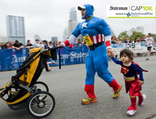 Felipe Vega and his daughter, Guilina, 2, approach the finish line of the 2013 Statesman Capitol 10,000 race on Sun., April 7, 2013. Ashley Landis for American-Statesman