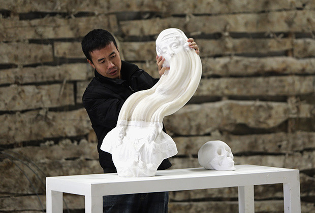 "Chinese artist Li Hongbo stretches a paper sculpture work at his studio on the outskirts of Beijing, January 20, 2014. Born into a simple farming family, Li said he had always loved paper, invented in ancient China. Beyond his sculptures, he has spent six years producing a collection of books recording more than 1,000 years of Buddhist art on paper. Neither plaster nor clay, the statues are concertinas of thousands upon thousands of fine pieces of paper.""At the beginning, I discovered the flexible nature of paper through Chinese paper toys and paper lanterns,"" Li, 38, told Reuters. Picture taken on January 20, 2014. REUTERS/Jason Lee (CHINA - Tags: SOCIETY TPX IMAGES OF THE DAY) - RTX17QXX"