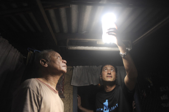"TO GO WITH AFP STORY by Karl Malakunas   -   FILES   -   Illac Diaz (R) inspects a solar light bulb with Siplicio Mondas, 73, installed by the Philippine army soldiers on a roof in a shanty town in Manila, with other private and government organization, they hope to install simultaneously around 10,000 solar bottle bulbs in the slum aria in Metro Manila on November 30, 2011 in a project called ""Liter of Light"".   Filipino social entrepreneur Illac Diaz is aiming to help a million poor people in a year, and with the help of some plastic bottles plus a savvy social media campaign may do even better. Diaz's project appears simple -- fill discarded soft drink bottles with water, place them in roofs of houses and allow the refracted light to brighten homes during the day instead of using electric bulbs.   AFP PHOTO / JAY DIRECTO (Photo credit should read JAY DIRECTO/AFP/Getty Images)"