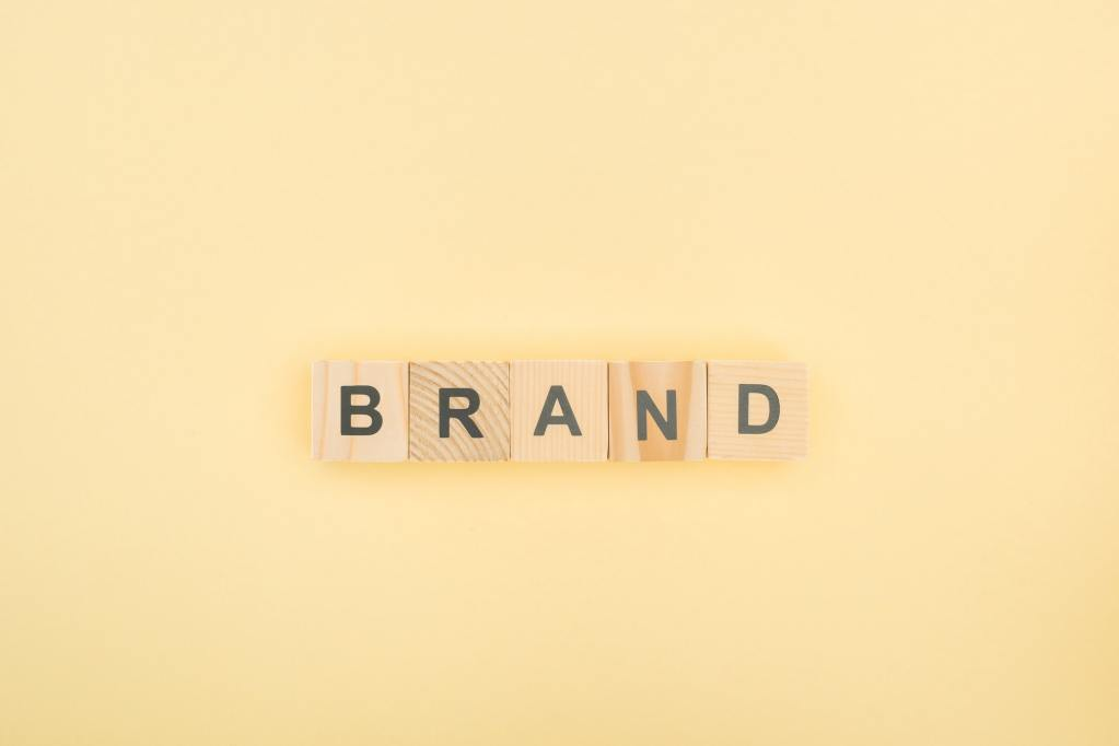 top view of brand lettering made of wooden cubes on yellow background