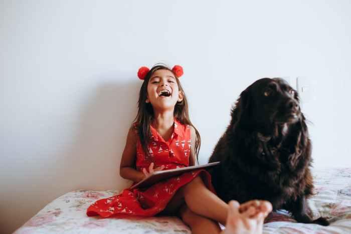 happy girl sitting beside black dog