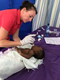 Karen feeding the baby with pneumonia. He improved a lot over the course of the week!