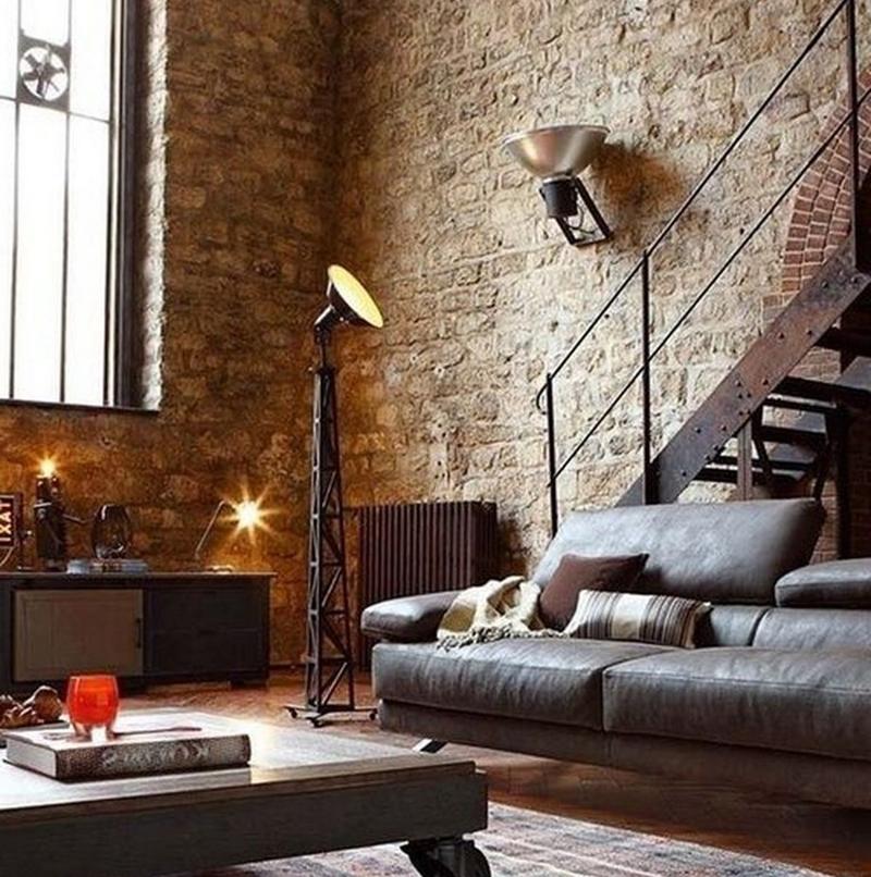 Luminária industrial do tipo holofote em um ambiente com paredes rústicas e decoração industrial