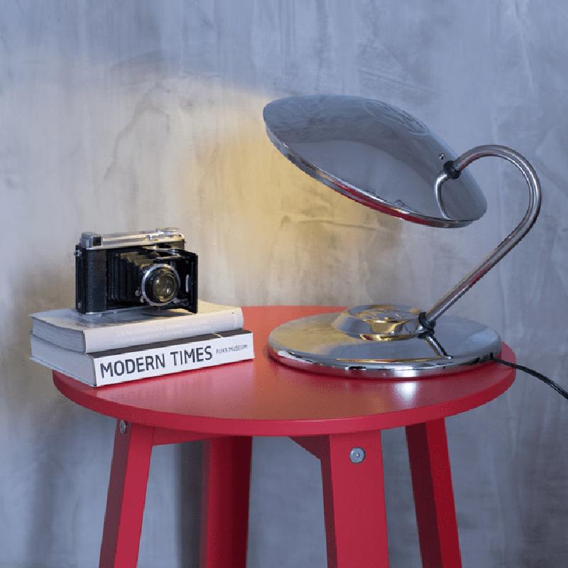 Luminária modelo Calota de Fusca em cima de uma mesinha lateral com decoração moderna e industrial