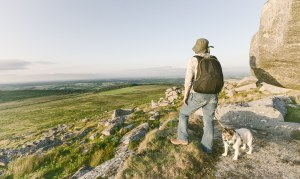 Woman hiking on Bodmin Moor in Cornwall with dog.