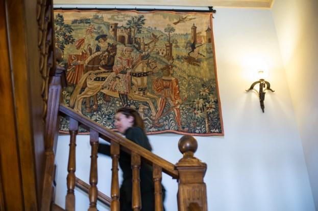 Escaleras de madera noble y tapiz antiguo.