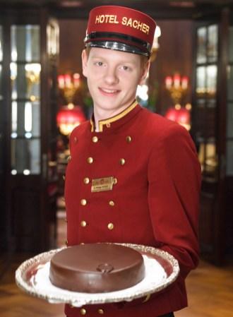 "Bell boy del hotel Sacher con la tarta ""Original Sacher-Torte""."
