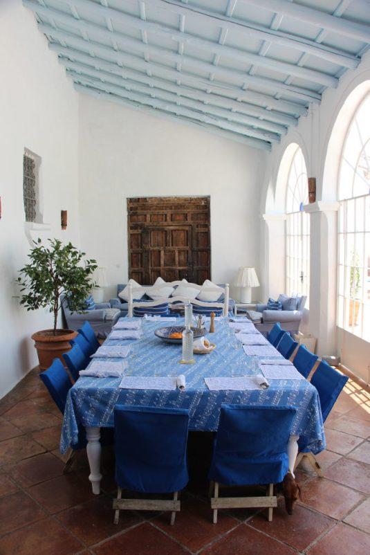 Una de las mesas para comer está en la galería junto a la piscina.