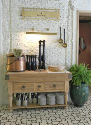 Sobre la mesa, pimenteros grandes y un parmigiano reggiano de varios kilos, típicos insumos de una trattoria u osteria.