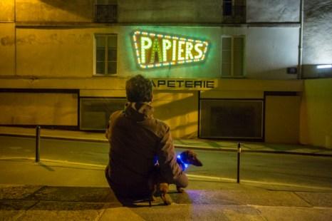 Eros con su collar de LED y el luminoso de la papelería Les P' tits Papiers, 2 Place Félix Fournier.