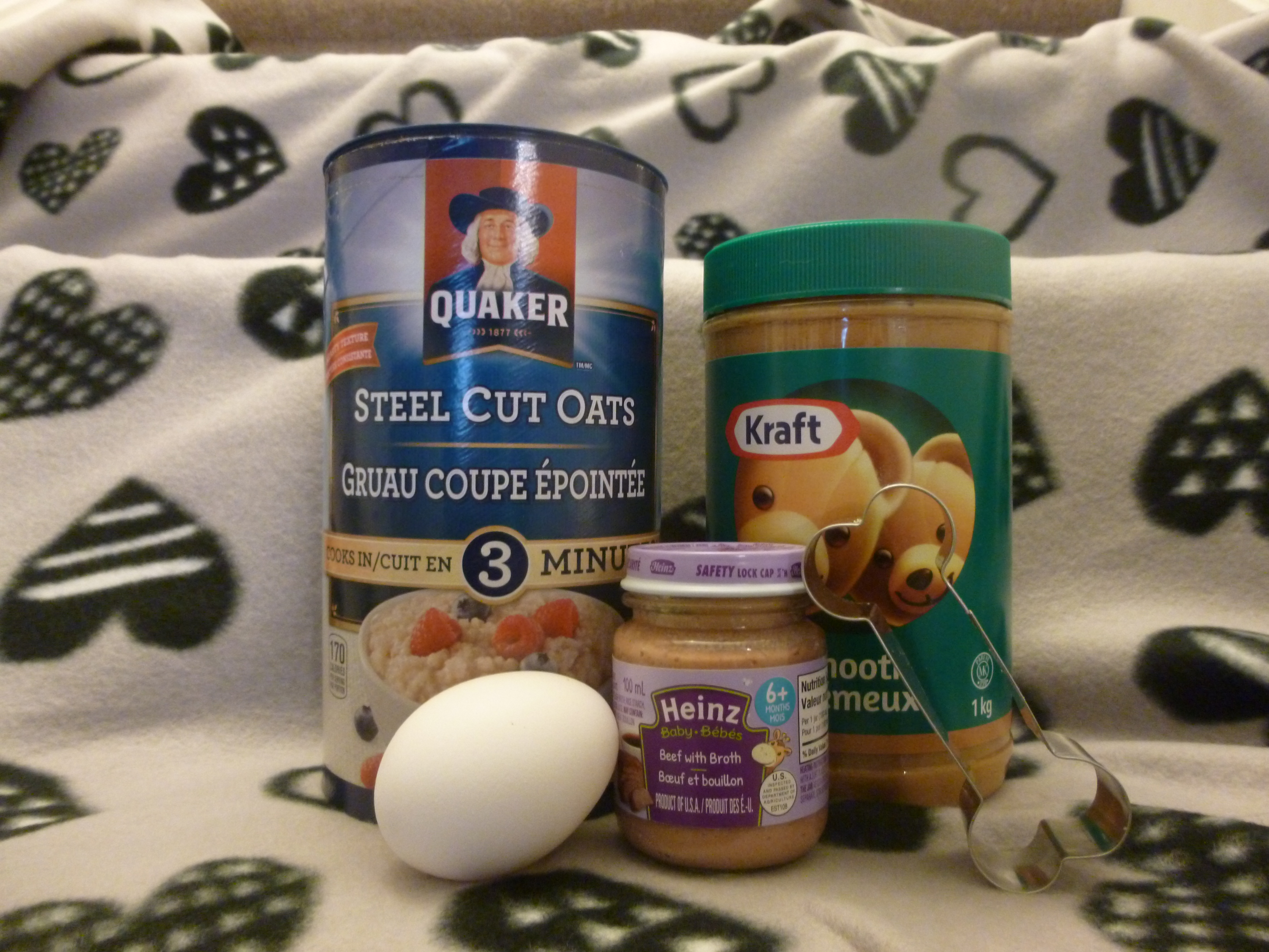 oats, peanut butter, an egg and baby food jar - all ingredients for dog treat recipe