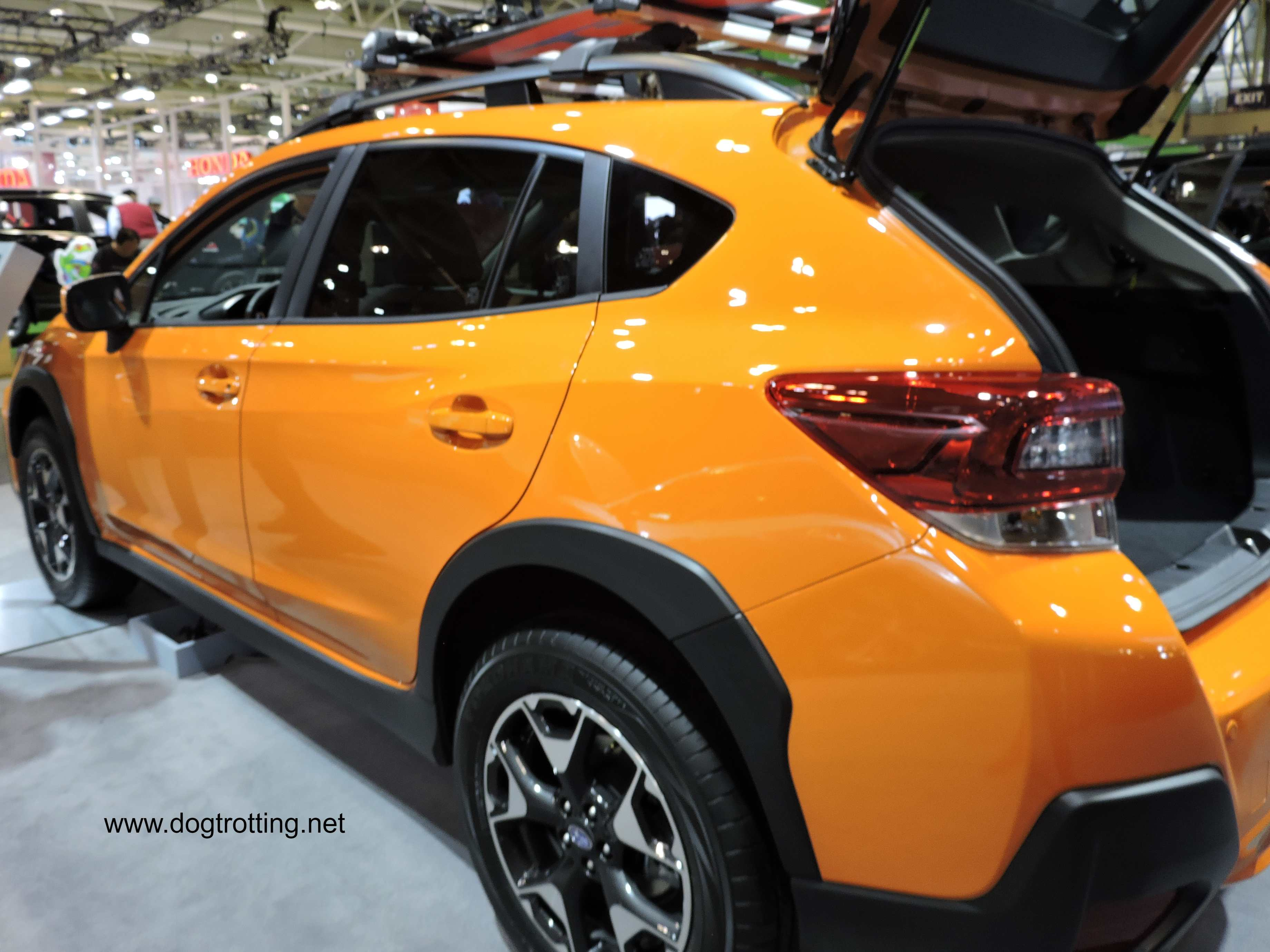 side of yellow Subaru car at auto show