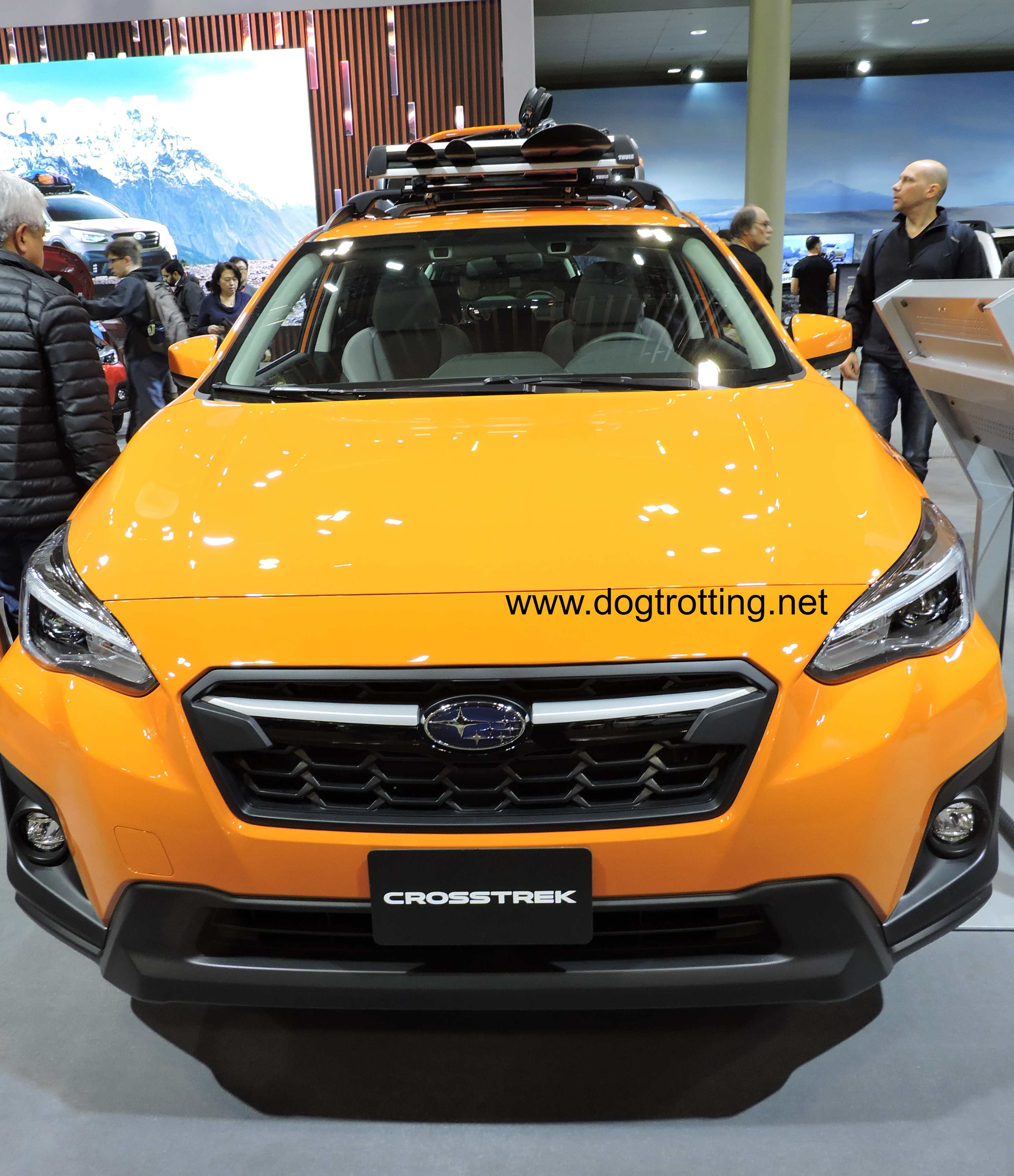 front of yellow Subaru at auto show