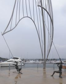 waterfront sculpture along Hamilton Harbour, Ontario. Male and female bronze figures struggle to hold a boat sail.