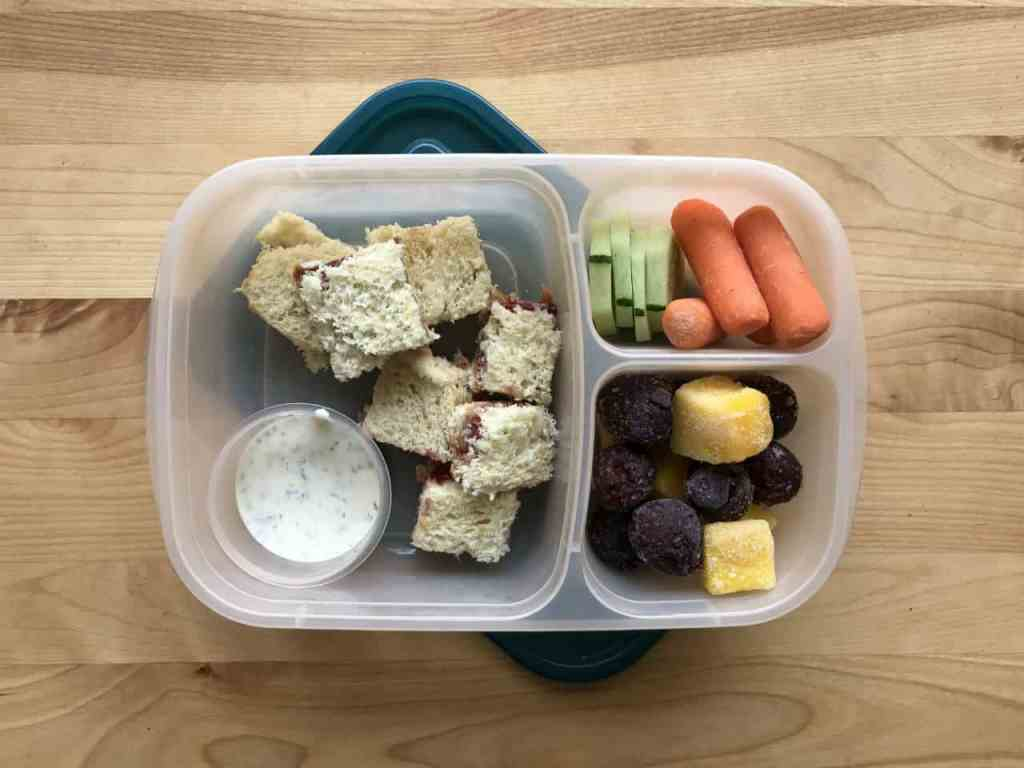 Homemade lunchable with peanut butter and jelly, carrots, cucumbers, mango, and cherries
