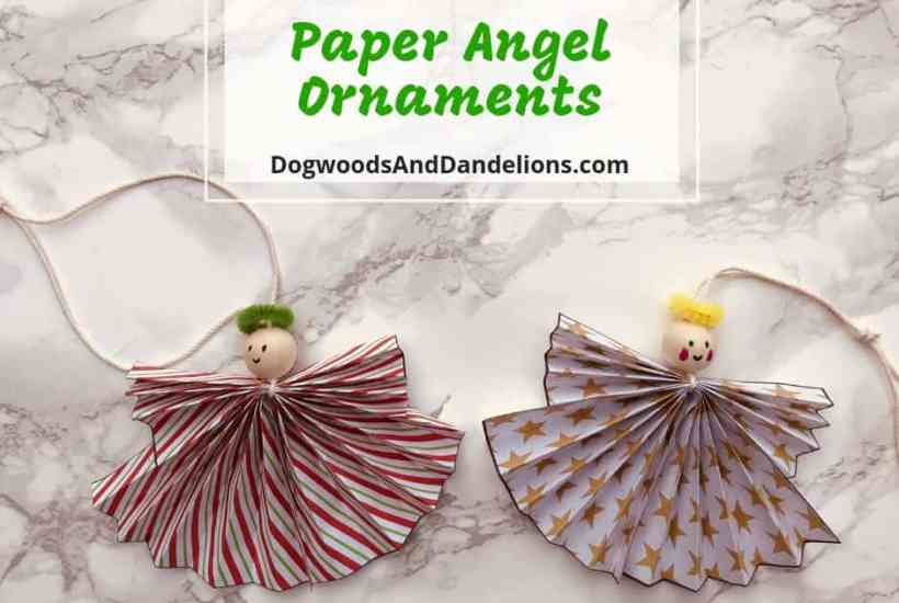 two paper angel ornaments on a marble background