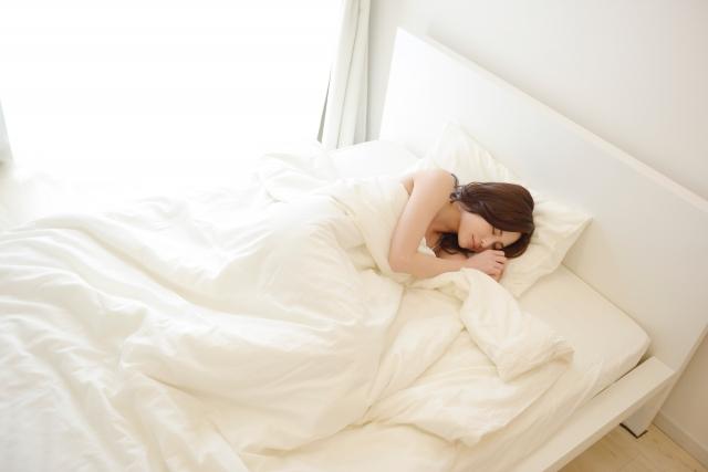 ベットで眠る女の人。羽毛布団が気持ちいい。
