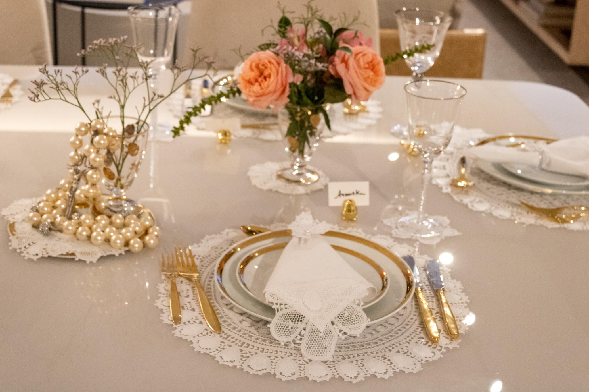 Mesa posta com renda Renascença, louças em porcelanas brancas com dourado, faqueiro, taças e peças decorativas  Virgínia Brandão